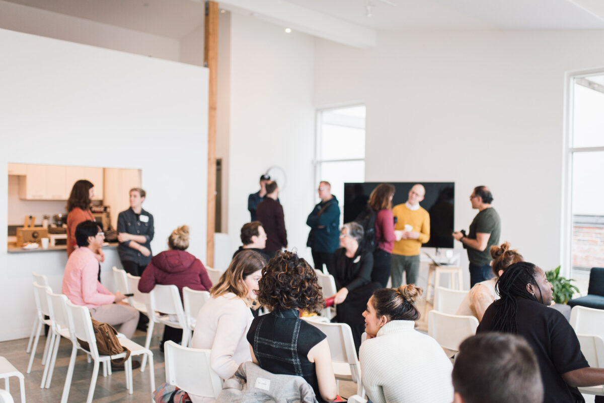 A group gathers in a workshop room